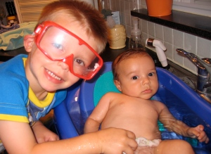 Big Brother Owen helping bathe his new brother Chase.